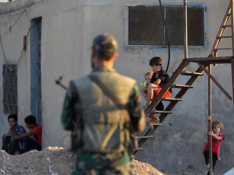Children watch as soldier stands guard outside of Damascus, Syria.
