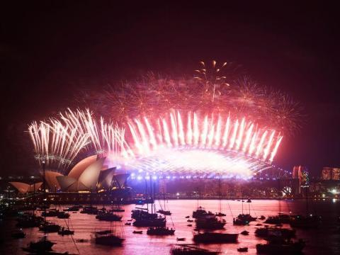 Fuegos artificiales por encima del Puente de la bahía Sídney y la Opera House en año nuevo.
