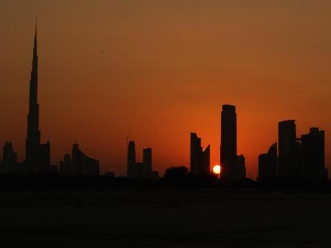 El sol se esconde tras el horizonte de Dubai, Emiratos Árabes Unidos.