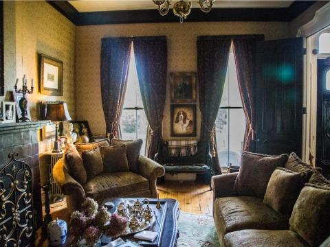 También se muestran los lujosos cojines y las pesadas cortinas color burdeos