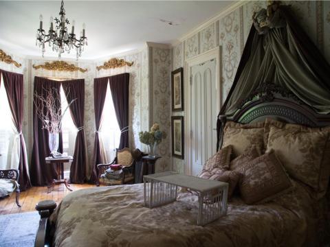 Otra de ellas tiene un candelabro y la pared está cubierta por un papel tapiz con estampado