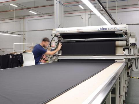 The fabric is laid out under large cutting machines, and the paper is placed on top.
