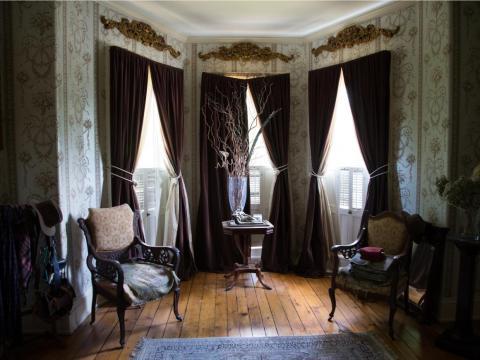 Apliques de oro cuelgan sobre los ventanales que están enmarcados por cortinas color burdeos