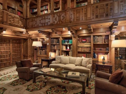 It includes an expansive, two-story library with hand-carved paneling and a detailed ceiling.