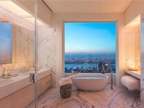 The luxurious master bathroom had marble floors and walls, cubic marble vanities with 22-inch oval sinks, custom wood cabinets, a large freestanding soaking tub, a shower, heated floors — and eye-popping views of the city.