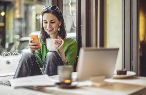 Una mujer mirando sus cuentas bancarias en el móvil.