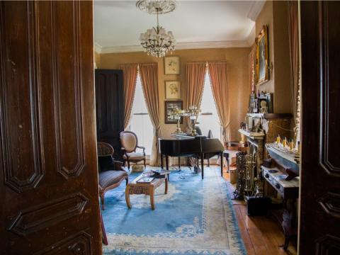 Uno de los salones principales tiene un piano y sillas para descansar o entretenerse en el tiempo libre