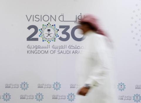 Un hombre saudí pasa junto al logotipo de Visión 2030 después de una conferencia de prensa, en Jeddah, Arabia Saudita, el 7 de junio de 2016.