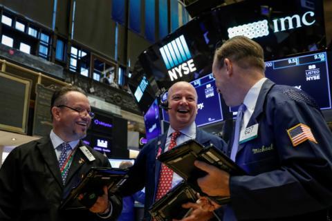 Traders sonrien operando en Wall Street