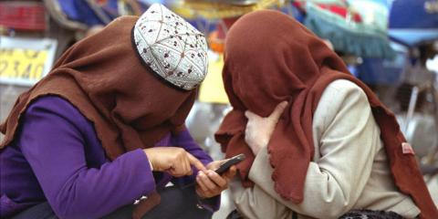 Uighurs in Xinjiang, western China, are subject to some of the most intrusive surveillance measures in teh world. Here, Muslim Uighur women on a cellphone in Kashgar, Xinjiang, in April 2002.
