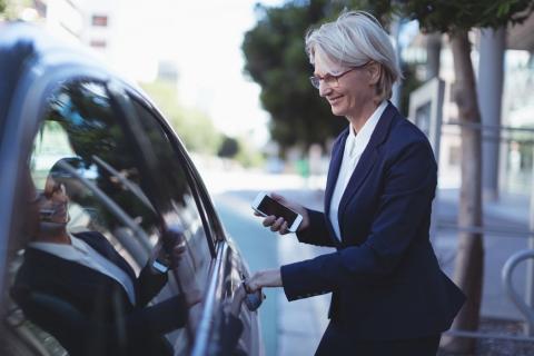 Una usuaria se sube a un vehículo de alquiler con conductor