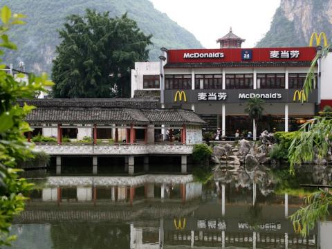 In Yangshuo, China, a McDonald's sits in a pagoda at the base of mountains and has beautiful water views.