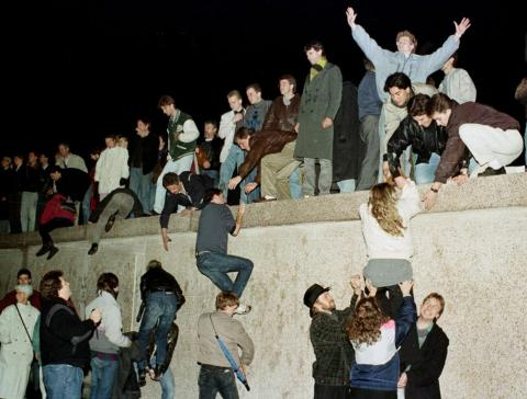 East Germans celebrated as they climbed the Berlin Wall at the Brandenburg Gate.