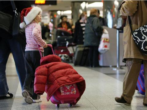 A girl traveling in a Santa hat.