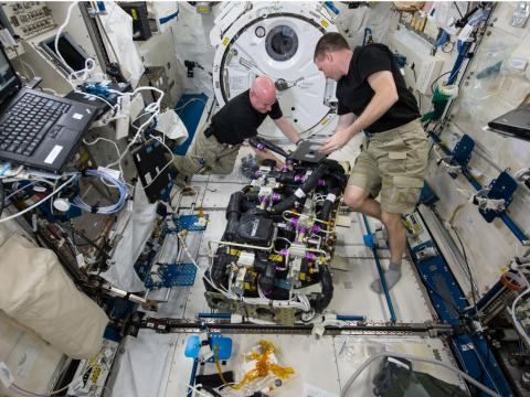 NASA astronauts Scott Kelly (left) and Terry Virts (right) work on a Carbon Dioxide Removal Assembly inside the station's Japanese Experiment Module.