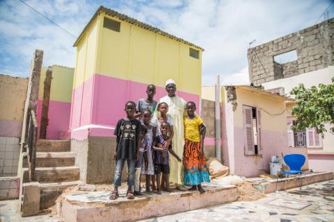 Malickane Gueye stands with his children in front of a newly constructed toilet at his home in Dakar, Senegal on September 25, 2018.
