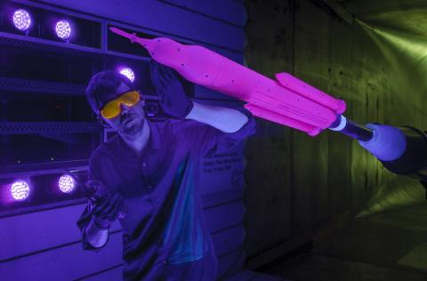 Patrick Shea inspects a 1.3% scale model of the NASA's Space Launch System (SLS) in a wind tunnel.