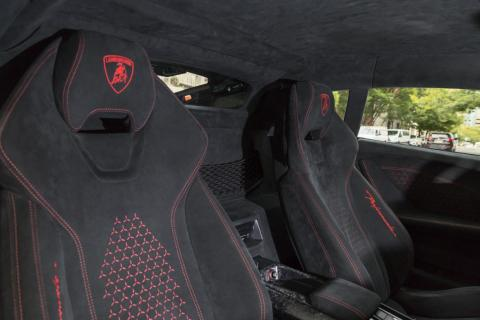"The red Lambo badging and stitching adds some flash to the otherwise monotonous ""Nero Cosmus"" interior."