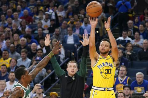Stephen Curry lanza a canasta con los Warriors.