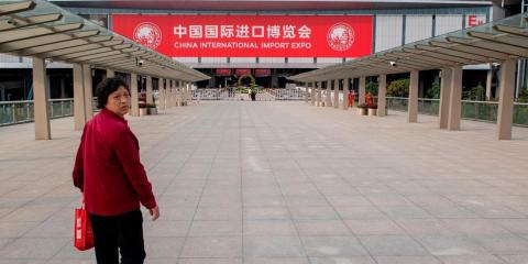 A woman walks towards the entrance of the National Exhibition and Convention Center (Shanghai), the main venue to hold the upcoming first China International Import Expo (CIIE), in Shanghai on October 31, 2018. - As China seeks to counter charges that its