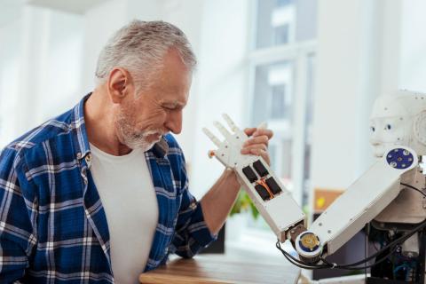 Un anciano prueba un robot humanoide
