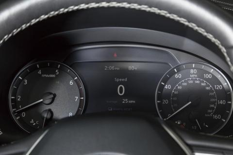 Beyond the steering wheel is a pair of concise analog gauges flanking a digital information display.