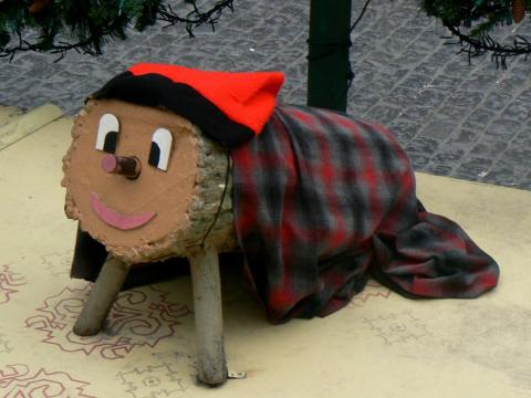 A Tió de Nadal figurine under a Christmas tree in Catalonian Spain.
