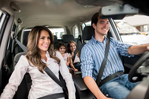 Un hombre conduce junto a su familia