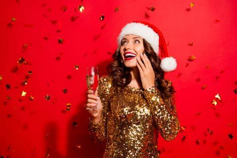 Una joven festeja la Navidad con una copa de champán