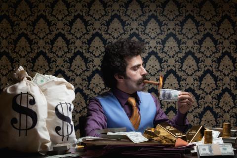 Un millonario se enciende un puro con un billete
