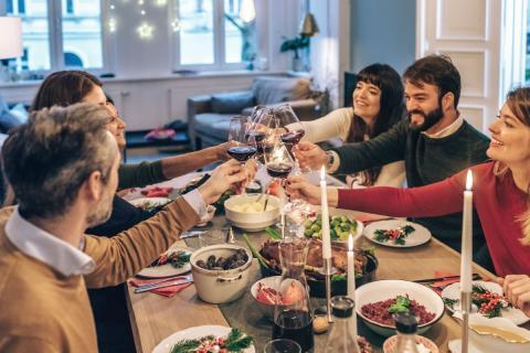 Personas chocan sus copas de vino durante una cena de Navidad