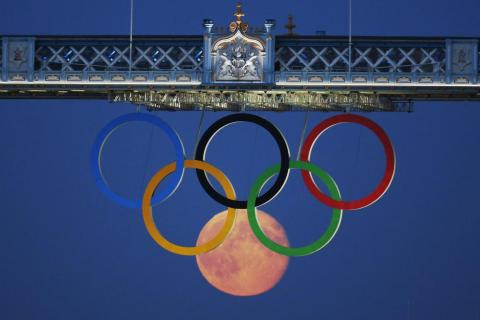 In a photo worthy of a gold medal, the full moon rose through the Olympic Rings hanging beneath Tower Bridge during the London 2012 Olympics.