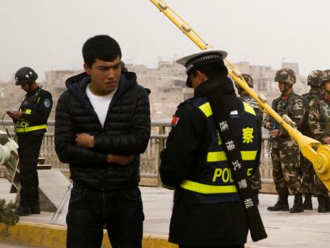 A police officer checks a Uighur man's ID documents in Kashgar, Xinjiang, in March 2017.