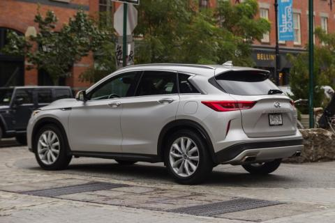 The rear end is dominated by the twin exhaust outlets, a subtle roof-top spoiler, and a liftgate.