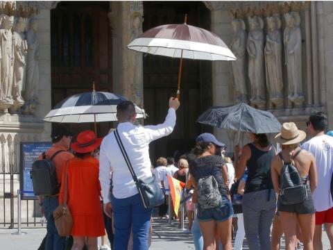 Un grupo de turistas españoles luchan contra el calor abrasador a las puertas de la Catedral de Nottre Dame, en París.
