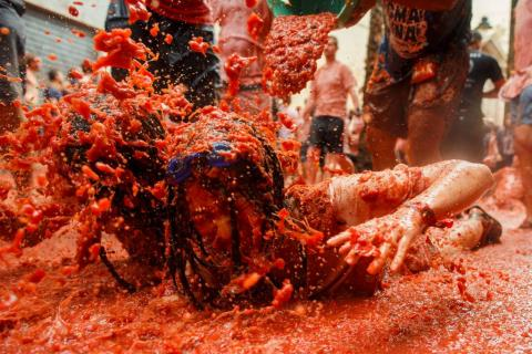 In Spain, revelers are covered from head to toe in tomatoes at La Tomatina festival.