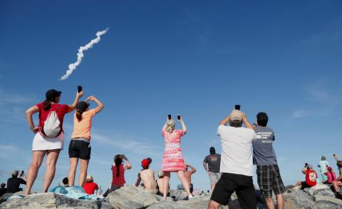Spectators at Cocoa Beach watch SpaceX's first Falcon Heavy rocket launch from the Kennedy Space Center on February 6, 2018.