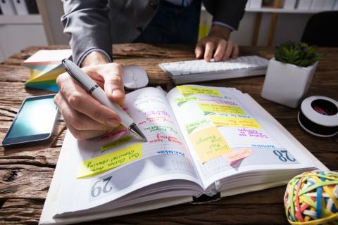 Un trabajador toma notas en su agenda