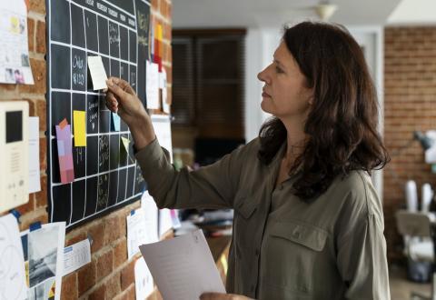 Una trabajadora revisa el calendario de trabajo de su oficina