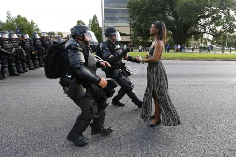 """A woman standing calmly, her long dress moving in the breeze, two police officers in full riot gear make their move,"" Reuters photographer Jonathan Bachman said of capturing this snapshot from a demonstration in Baton Rouge."