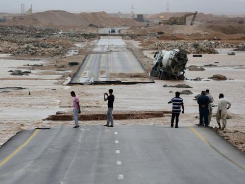 La gente visita una carretera cortada por las fuertes lluvias.