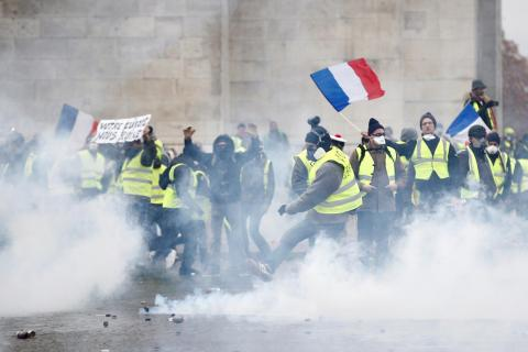 Protesters wearing yellow vests, a symbol of a French drivers' protest against higher diesel taxes, face off with French riot police during clashes at the Place de l'Etoile near the Arc de Triomphe in Paris, France, December 1, 2018.