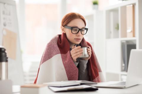 Mujer joven con frío en casa