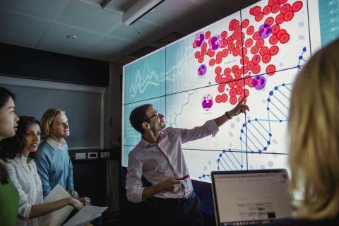 Un hombre muestra una estadística a sus colegas.