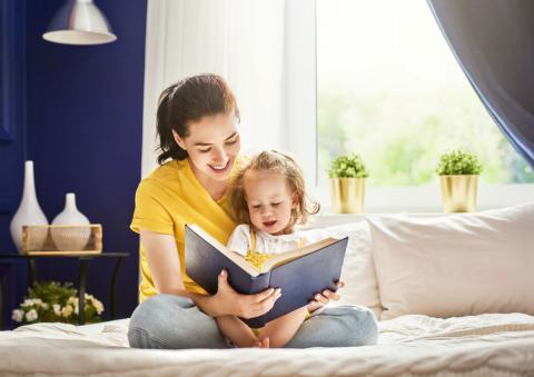 Una mujer lee junto a su hija