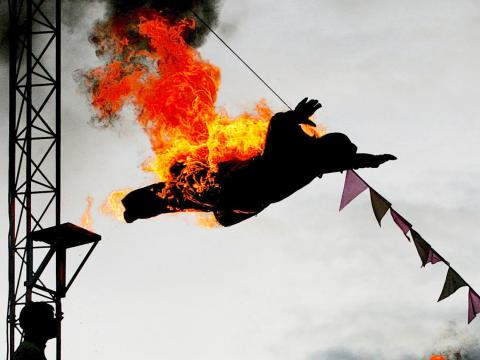 An acrobat sets himself on fire before diving into a swimming pool as part of a show.