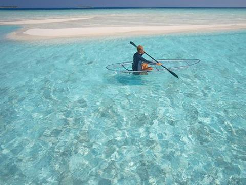 ... and paddling the clear blue waters in a translucent canoe.