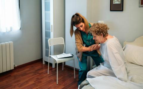 Una mujer sanitaria ayuda a una mujer mayor a levantarse.