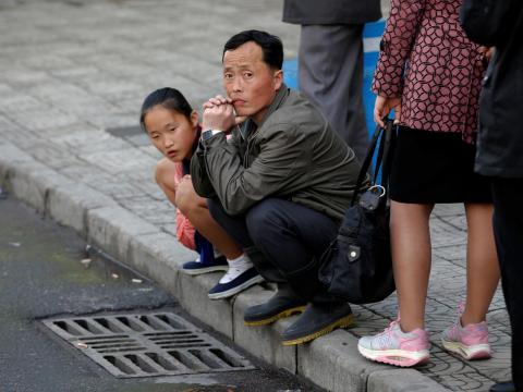 Here, people wait for a bus in central Pyongyang.