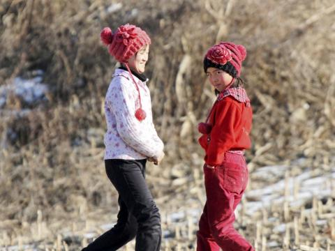Here, two girls walk along an alley on the banks of Yalu River in Sakchu county.